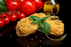 Round balls of pasta with tomatoes,basil,olive oil on black Royalty Free Stock Photography