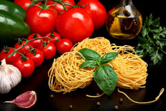 Round balls of pasta with tomatoes,basil,olive oil on black Royalty Free Stock Photo