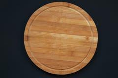 Round bambusowa tnąca deska na ciemnym tle, odgórny widok obrazy royalty free
