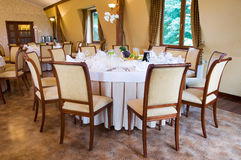 Round banquet table in brown. Round banquet table with chairs by window royalty free stock photos