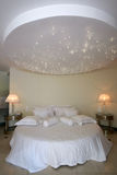 Round bed with stars lamp on the ceiling. Kingsize round bed with stars lamp on the ceiling in luxury hotel Stock Photo