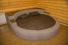 Round bed in a wooden bedroom Royalty Free Stock Photography