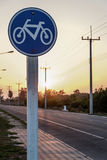 Round bicycle lane sign. On sunset background Stock Images