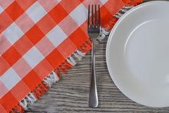 Round bielu pusty talerz, rozwidlenie i w kratkę tablecloth na drewnianym, zdjęcia stock