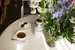 Round bielu stół z bukietem kwiaty, filiżanki herbata i cukierek, Fotografia Stock