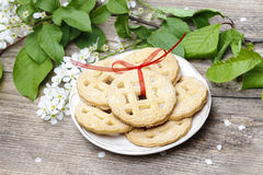 Round biscuits with red bow in spring setting Royalty Free Stock Photo