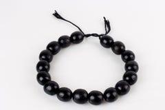 Round black beads on white background Stock Images