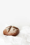 Round black bread lies on crumpled white paper on a white backgr. Ound. Space for text, daylight Stock Images