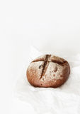 Round black bread lies on crumpled white paper on a white backgr. Ound. Space for text, daylight Stock Photography