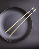 Round black plate with chopsticks for sushi Stock Photos