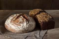 Round and black square bread loaf and wooden background.  Royalty Free Stock Photo