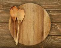 Round board and wooden spoons Royalty Free Stock Photography