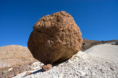 Round boulder held by a rock on slope Royalty Free Stock Photography