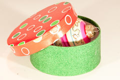Round box with Christmas tree decor ball. One round decorated gift box with red dotted lid has a holiday decor inside under the lid. Lid has red, white and green Stock Photography