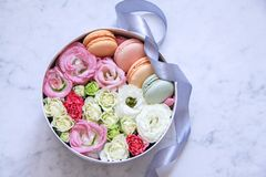 Round Box with flowers and almond cookies on marble background royalty free stock images