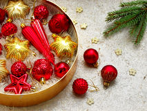 Round box with red and gold Christmas decorations. New Year and Xmas card background. Copy space. Selective focus. Stock Photos