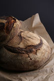 Round bread dark loaf on Food paper, black background. Stock Photos