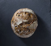 Round bread loaf on Black Slate Board. Royalty Free Stock Images