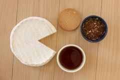 Round brie cheese with cup of tea, biscuit and tea leaves in a bowl on wooden background. Top view modern minimalistic image. Round brie cheese with cup of tea royalty free stock photo