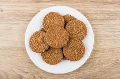 Round brown biscuits in white plate on wooden table Stock Photos