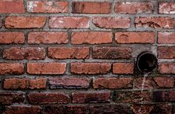 Round Brown Pipe Drainage With Liquid in Brown Bricked Concrete Wall Royalty Free Stock Image
