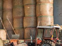 Round Bundles of Haystacks and Tractor in Countryside Location Stock Photography