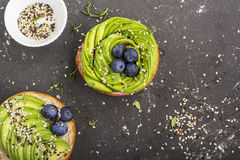 Round buns for breakfast with avocado in the form of a rose with a sauce of yogurt with a variety of sesame seedsAgainst Royalty Free Stock Images