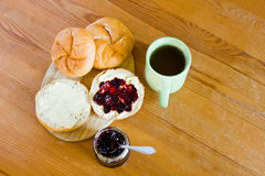 Round buns, butter, jar with currant jam and cup of tea. Royalty Free Stock Image