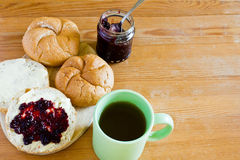 Round buns, butter, jar with currant jam and cup of tea. Royalty Free Stock Images