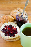 Round buns, butter, jar with currant jam and cup of tea. Royalty Free Stock Photos