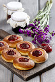 Round buns with plum on wooden table Royalty Free Stock Photos