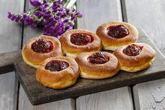 Round buns with plum on wooden table Royalty Free Stock Photo