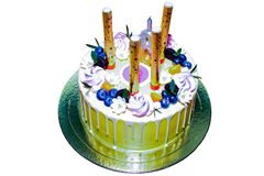 Round cake with candles fireworks with flowers and blueberries on top on a white background. stock images