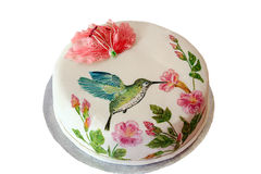 Round cake with fondant and painted humming-bird. And flowers stock photo