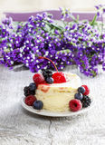 Round cake with fresh fruits. Purple flowers in the background. Selective focus Royalty Free Stock Photos