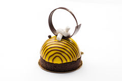 Round cake in a glaze in the form of a bee with a chocolate ring Stock Photos