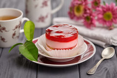 Round cake with raspberry jelly and cream. Cake in a plate on the wooden table, flowers and a cup of tea Royalty Free Stock Image