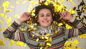 Round camera movement: Happy smiling girl lying on the floor, the golden confetti falling on her. Slow motion shot.  stock video