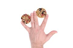 Round candied seeds and nuts in hand. Stock Photos