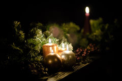 Round candles against festive green garland Stock Photos