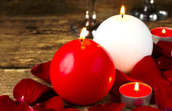Round candles in rose petals, romantic evening for Valentine, space for text. Selective focus Royalty Free Stock Image