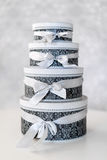 Round celebration gift boxes with silver ribbon bows on white table. Stack of presents in luxury interior. Royalty Free Stock Photos