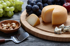 Round cheese with grapes on wooden backround Stock Photos