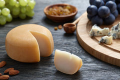 Round cheese with grapes on wooden backround Royalty Free Stock Photo