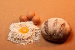 Round chleb, trzy jajka i jajecznego yolk otaczający mąką, Obrazy Stock