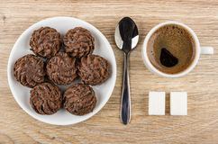 Round chocolate cakes in saucer, black coffee, sugar and spoon Royalty Free Stock Photo