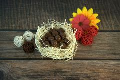Round chocolates in a nest of straw, multicolored decorative balls and flower buds on a wooden table royalty free stock photo