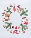 Round Christmas frame layout composition with green fir brunches, craft paper tags, holiday cookies stock image