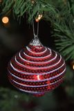 Striped Christmas ornament hanging in tree. Round Christmas ornament hanging onto a Christmas tree. A Colorful handmade design stock photography