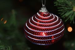 Striped Christmas ornament hanging in tree. Round Christmas ornament hanging onto a Christmas tree. A Colorful handmade design stock photo